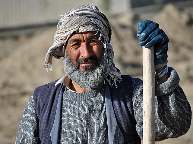 """Ów robotnik, pracujący przy budowie drogi na przedmieściach Ghazni, nie uciekał przed obiektywem. Widząc jego twarz, przypomniała mi się rozmowa sprzed kilku lat, jaką odbyłem z dyrektorem jdnego z kabulskich szpitali. """"Większość tych mężczyzn..."""" - mówił wówczas, wskazując na grupę pacjentów - """"nie ma więcej niż czterdzieści parę lat. A wyglądają na 20 lat starszych. Afganistan to piękny, ale i okrutny wobec własnych mieszkańców kraj...""""/fot. Marcin Ogdowski"""