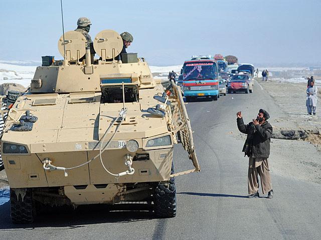 """""""Masz ognia?"""" w wersji afgańskiej. Po prawej stronie straszy wyrwa po zdetonowanym IED. Droga Ghazni-Wagez/fot. Marcin Ogdowski"""