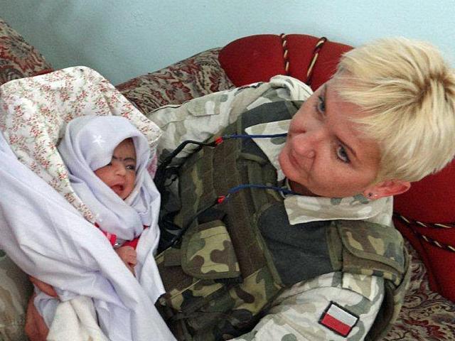 Pielęgniarka, sierżant Elżbieta Grodzka, z dzieckiem na ręku/fot. Marcin Gil