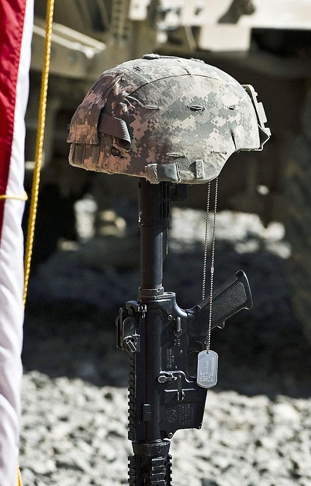 Hełm na karabinku - tak żegnają poległych kolegów żołnierze/fot. Adam Roik