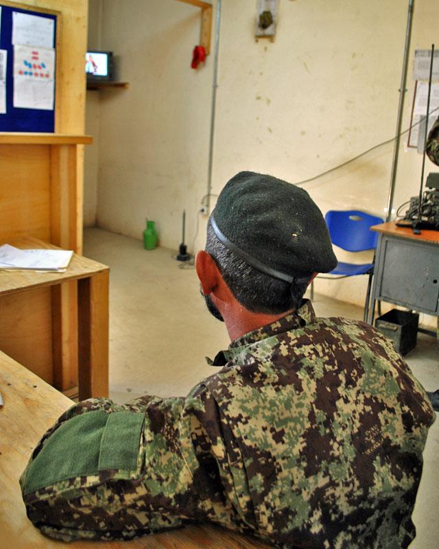 """To widok tego mężczyzny – oficera pełniącego służbę w centrum operacyjnym jednej z brygad ANA – po raz kolejny skłonił mnie do rozważań nad istotą afgańskiego konfliktu. Nad faktem, iż dla większości Afgańczyków toczy się on gdzieś obok. Owszem, ma wpływ na ich codzienność, ale został – jak to się mądrze mówi w socjologii – zinternalizowany, """"oswojony"""", uznany za coś oczywistego, z czym da się żyć. Mężczyzna na zdjęciu jak gdyby nigdy nic oglądał sobie mecz piłki nożnej na telewizorze schowanym w kantorku. Futbol – szczególnie po ostatnich sukcesach afgańskiej kadry – staje się w tym kraju niezwykle popularną i ważną dyscypliną. W zestawieniu z kolejnym meczem wojna – jak widać – schodzi na plan dalszy…"""