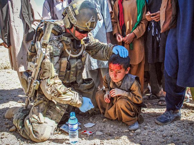 """O takich zdjęciach często mówiło się """"ustawki"""". """"Ustawki"""", które miały """"poprawić wizerunek żołnierzy polskich, służących w Afganistanie"""". Bzdura. Oczywiście, tego typu fotografie można w taki właśnie sposób wykorzystać, co nie zmienia faktu, że powstały zupełnie spontanicznie. Uprzedzając zaś komentarze – nie wierzę, by żołnierskie reakcje były inne, gdyby nie moja obecność. Nz. ratownik medyczny Zespołu Bojowego """"Charlie"""" XIII zmiany udzielający pomocy poturbowanemu przez kolegów 6-latkowi. PS. Właśnie to zdjęcie planowałem wykorzystać jako okładkę do """"(Nie)potrzebnych"""". Zwyciężyła jednak koncepcja rysunkowa. Prowincja Ghazni, jesień 2013/fot. Marcin Ogdowski"""