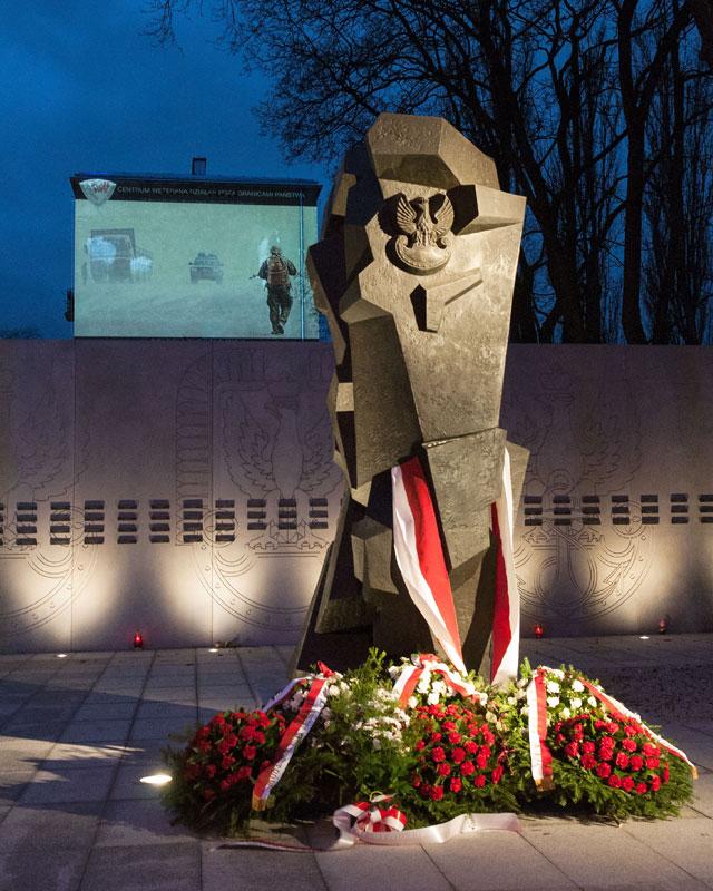 """Pomnik i mur z nazwiskami poległych """"misjonarzy"""". Wczoraj, przy okazji otwarcia Centrum Weterana, na ścianie pobliskiego budynku wyświetlano również zdjęcia z albumu """"Polski Afganistan""""/fot. Michał Zieliński"""